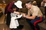 2nd Lt. Marc Martinez, a platoon commander with 3rd Battalion, 6th Marine Regiment, helps a girl complete an ice breaking exercise during an effort to bring aid and support to children in need at Times Square Church in New York, May 28, 2016. Fleet Week New York is an opportunity for the public to interact with service members from America's sea services, spreading awareness of the Navy and Marine Corps' missions at home and abroad. Photo by Cpl. Jared Lingafelt