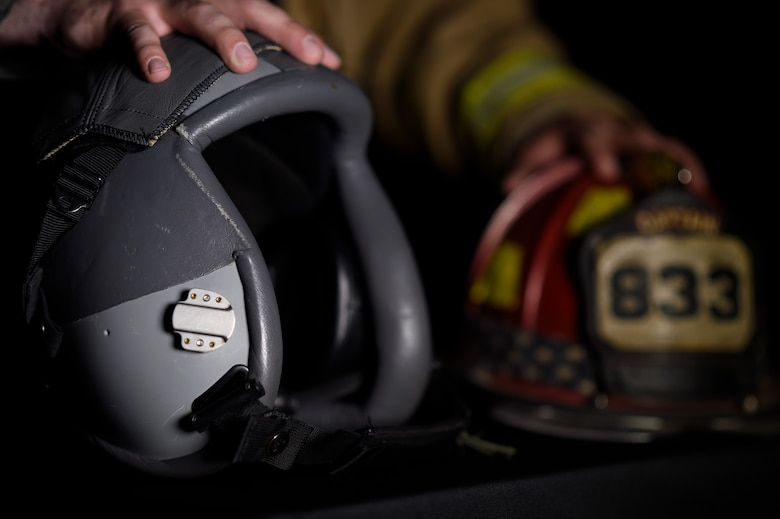 Staff Sgt. Garrett Christensen, 56th Civil Engineer Squadron logistics NCO in charge, displays safety gear from his current job as a fire fighter and his dream job of a fighter pilot April 14, 2016 at Luke Air Force Base, Ariz. Christensen has been selected for Basic Officer Training School with the ultimate goal of becoming a fighter pilot.  (U.S Air Force photo by Staff Sgt. Staci Miller)
