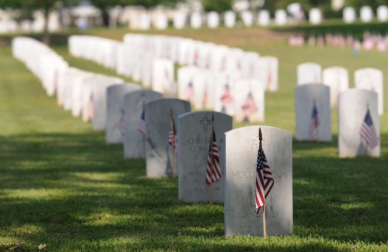 U.S. flags are displayed in front of tombstones during a Memorial Day Ceremony May 30, 2016, Biloxi, Miss. Local veterans, family members and Keesler Air Force Base personnel attended the event at the Biloxi National Cemetery to honor and remember the lives of fallen heroes of the U.S. military. (U.S. Air Force photo by Kemberly Groue)