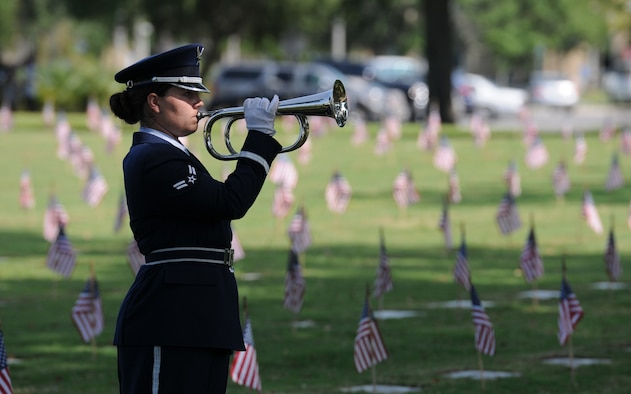 Airman 1st Class Brittany Harkins, Keesler Honor Guard member, plays taps during a Memorial Day Ceremony May 30, 2016, Biloxi, Miss. Local veterans, family members and Keesler Air Force Base personnel attended the event at the Biloxi National Cemetery to honor and remember the lives of fallen heroes of the U.S. military. (U.S. Air Force photo by Kemberly Groue)