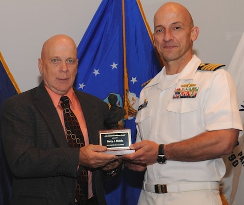 "DAHLGREN, Va. - Naval Surface Warfare Center Dahlgren Division (NSWCDD) Commanding Officer Capt. Brian Durant presents Barry Mohle with the John Adolphus Dahlgren Award for sustained leadership and technical excellence across the test and evaluation community at the NSWCDD Annual Honor Awards ceremony on May 18, 2016. ""Mr. Mohle's commitment to implementation of robust business practices, technological advances and workforce development ensures the continued excellence of our test and evaluation workforce's contributions to the Navy,"" according to the citation."