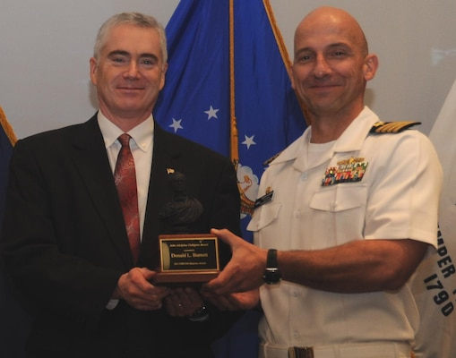 "DAHLGREN, Va. - Naval Surface Warfare Center Dahlgren Division (NSWCDD) Commanding Officer Capt. Brian Durant presents Dohn Burnett with the John Adolphus Dahlgren Award for his years of exceptional technical and organizational leadership of NSWCDD at the command's Annual Honor Awards ceremony on May 18, 2016. ""Mr. Burnett achieved numerous technical milestones throughout his exemplary career, including the integration and installation of the Aegis Baseline 9 combat system, basis cyber capability integration, establishment of the Fast Frigate Program, and the foundation for integration of railgun and laser systems into surface combatants,"" according to the  citation."