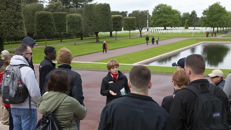 A French tour guide talks to Marines from Headquarters and Service Battalion, Headquarters Marine Corps, Henderson Hall and Marine Barracks Washington, D.C, at Normandy American Cemetery and Memorial in Coleville sur Mer, France, May 25, 2016. The cemetery overlooks Omaha Beach and is the final resting place of more than 9,000 American service members and honors more than 1,500 American service members who are missing in action.