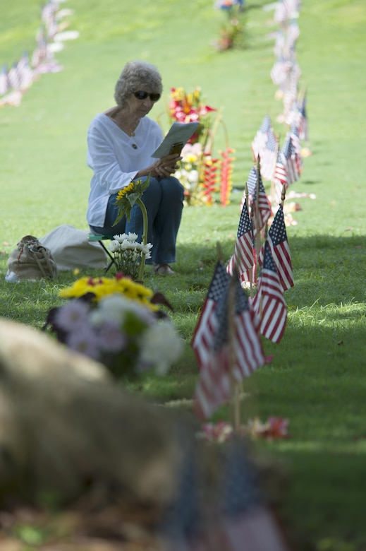 160531-N-UG232-199 Honolulu, Hawaii (May 31, 2016) Barbara Loveless reads the program for the Honolulu Mayor's Memorial Day Ceremony at the National Memorial Cemetery of the Pacific. Ms. Loveless sat by the grave site of her husband, U.S. Army Cpl. Robert Loveless, during the ceremony.  Cpl. Loveless served during World War II and died in 2009.