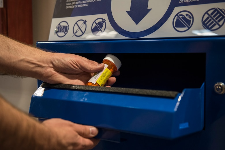 PETERSON AIR FORCE BASE, Colo. – A patient disposes of old medication at the MEDSAFE disposal box located in the lobby of the Peterson Air Force Base Clinic on May 24, 2016. This box and another at the satellite pharmacy located in the base exchange, provide a safe way to keep unsafe substances from falling into the wrong hands. (U.S. Air Force photo by Senior Airman Rose Gudex)