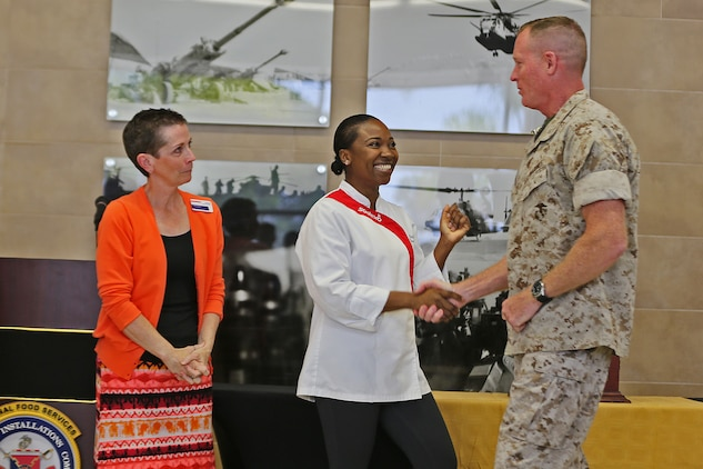 Jackie Murphy, 31 Area Mess Hall General Manager, and Natalie Williams, 31 Area Mess Hall Production Manager, shake hands with Brig. Gen. Edward D. Banta, Commanding General, Marine Corps Installations-West, Marine Corps Base Camp Pendleton, during a ceremony naming Camp Pendleton's 31 Area Edson Range Mess Hall the Maj. Gen. William Pendleton Thompson Hill Award winners for best full food service mess hall in the Marine Corps, May 31.   The W.P.T. Hill Award was established in 1985 to improve food service operation and recognize the best messes in the Marine Corps.