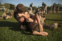 Marines grapple during squad-on-squad ground fighting at Robertson Barracks, Northern Territory, Australia, on May 25, 2016. Squads had to win two bouts or flip tires in order to move on to the next station during the squad competition. The squad-level competition determined which rifle squad or weapons platoon section had the best physical fitness, small-unit leadership, and cohesion within Company C, 1st Battalion, 1st Marine Regiment, Marine Rotational Force - Darwin.