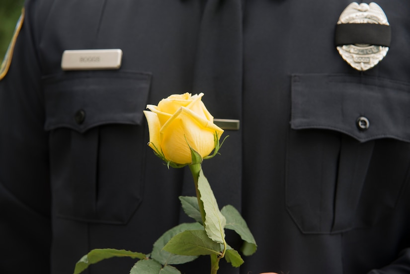 A Charleston police officer holds a single yellow rose in remembrance of his fellow co-worker, Detective Sergeant Christopher Kelley.  A yellow rose is often presented to honor and remember a friendship.  In honor of Police Week, the 628th SFS collaborated with multiple base agencies to conduct various events to remember and celebrate their fallen brothers and sisters in law enforcement. (U.S. Air Force Photo/Airman 1st Class Haleigh Laverty)