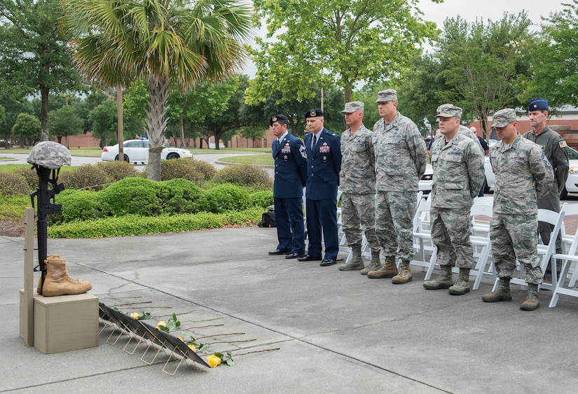 Joint Base Charleston leadership stand for a moment of silence to honor the fallen defenders during the National Police Week ceremony May 20, 2016, at the base flag pole on Joint Base Charleston – Air Base, S.C.  In honor of Police Week, the 628th SFS collaborated with multiple base agencies to conduct various events to remember and celebrate their fallen brothers and sisters in law enforcement. (U.S. Air Force Photo/Airman 1st Class Haleigh Laverty)