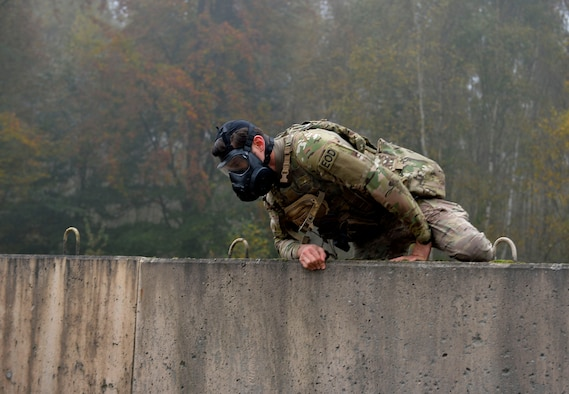 An explosive ordnance disposal Airman with the 786th Civil Engineer Squadron climbs over a wall during a special ruck and run event in support of the Combined Federal Campaign. The 786th CES's EOD flight conducts ruck marches at the last Friday of every month. (U.S. Air Force photo by Airman 1st Class Joshua Magbanua)