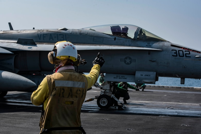 Petty Officer 3rd Class Gabrielle Embry signals to an F/A-18F Super Hornet, assigned to Strike Fighter Squadron (VFA) 131, on the flight deck of the aircraft carrier USS Dwight D. Eisenhower (CVN 69) (Ike). Embry serves as an aviation boatswain's mate (handling) aboard Ike. Ike and its carrier strike group are deployed in support of Operation Inherent Resolve, maritime security operations and theater security cooperation efforts in the U.S. 5th Fleet area of operations. (U.S. Navy photo/Petty Officer 3rd Class Nathan T. Beard)