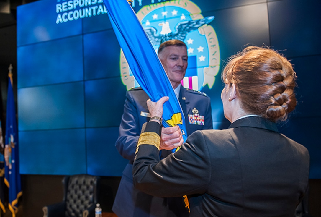 Air Force Lt. Gen. Andy Busch presents the colors of DLA Land and Maritime to new commander Rear Adm. Michelle Skubic Oct. 31 in the Land and Maritime Operations Center auditorium. The colors changing hands signifies the transfer of total authority and accountability from James McClaugherty to Skubic.