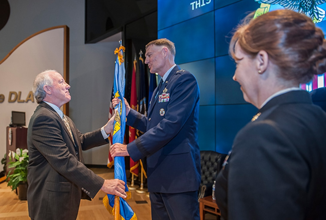 James McClaugherty passes the organization's colors to Air Force Lt. Gen. Andy Busch, DLA director, during a change of command ceremony Oct. 31 in the DLA Land and Maritime Operations Center auditorium. McClaugherty transferred command to Navy Rear Adm. Michelle Skubic.