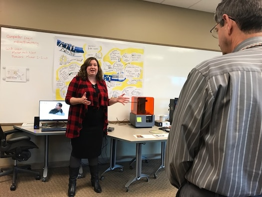 AFRL Maker Hub director Dr. Emily Ferhman Cory, describes to attendees how the desktop 3-D printing machine works at the AFRL Maker Hub grand opening held on October 27, 2016. (U.S. photo/Stacey Geiger)