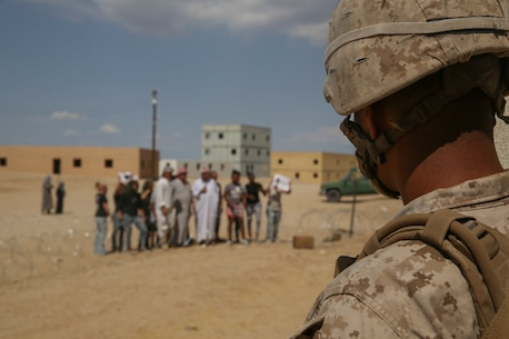 Corporal Christopher Ponce, a team leader with 3rd Battalion 7th Marine Regiment, stands at the corner of a building monitoring protesters during the battalion's certification exercise aboard Marine Corps Air-Ground Combat Center Twentynine Palms, Calif., Aug. 22, 2016. U.S. Marine Corps photo by Cpl. Timothy Valero