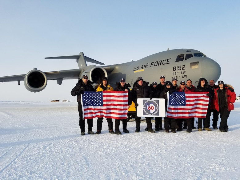 "The crewmembers of ""ICE12"" and Team McChord Airmen display the U.S. flag Oct. 21, 2016, at McMurdo Station, Antarctica. ICE12 commemorated the first ever Air Force Antarctic flight flown 60 years ago. (Courtesy photo)"