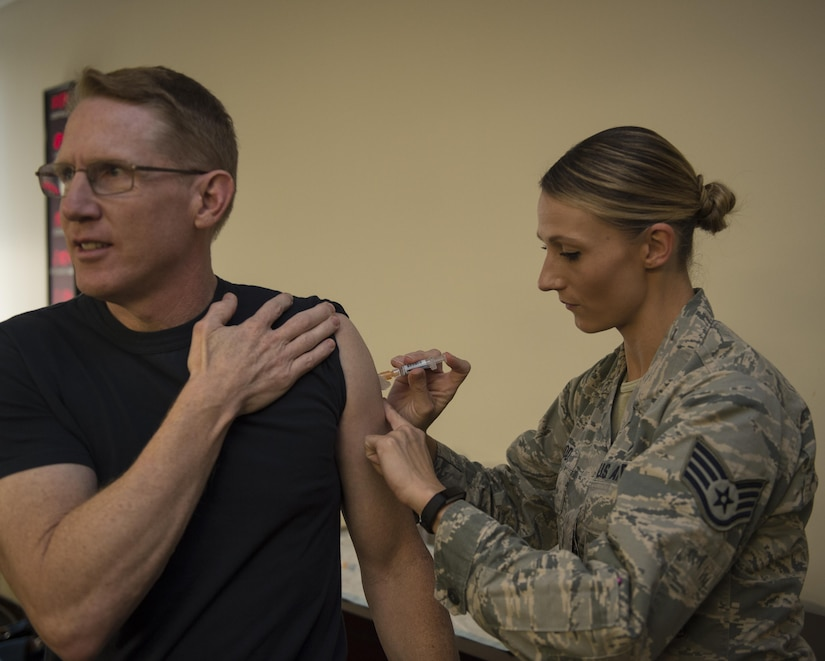 U.S. Navy Capt. Robert Hudson, left, Joint Base Charleston deputy commander, receives his annual flu shot from Staff Sgt. Sarah Woods, right, 628th Medical Group (MDG) NCO in charge of the allergy and immunizations clinic, Oct. 21. The 628th MDG began offering the flu shot to active-duty service members, children from ages three to 17 and high-risk adults Oct. 17. Beginning Nov. 1, the influenza vaccine is available to all DoD beneficiaries. Additionally, the Air Base Exchange will offer a flu line on Nov. 19 from 1000 to 1300.