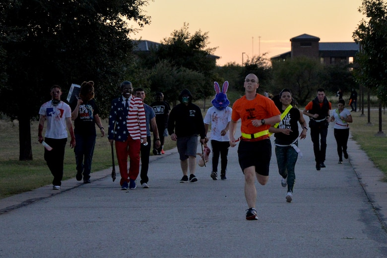 """Participants of the purge 5k run from volunteers in costumes during Ghoulfellow on Goodfellow Air Force Base, Texas, Oct. 28, 2016. The purge 5k featured """"adversaries"""" who attempted to grab flags on each runner. (U.S. Air Force photo by Airman 1st Class Randall Moose/Released)"""