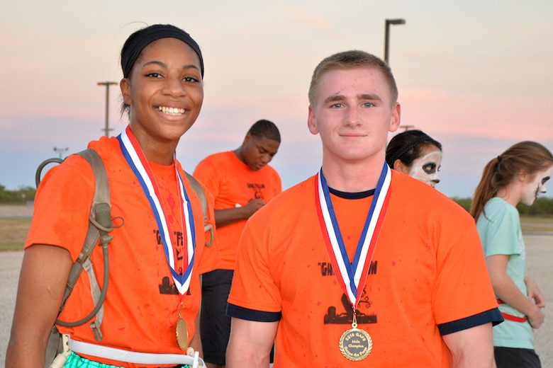 U.S. Army Pvt. Jayda James, 344th Military Intelligence Battalion student, and U.S. Air Force Airman Nicholas Trackwell, 312th Training Squadron student, display their medals after winning the purge 5k during Ghoulfellow on Goodfellow Air Force Base, Texas, Oct. 28, 2016. The runners with the fastest time and the most flags won the race. (U.S. Air Force photo by Airman 1st Class Randall Moose/Released)