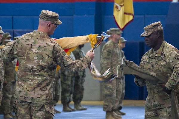 Col. Stephen M. Bousquet, commander of the 369th Sustainment Brigade, 1st Sustainment Command (Theater), and Command Sgt. Maj. Anthony V. Mclean, the brigade's senior enlisted advisor, uncase the brigade's unit colors during a ceremony held at Camp Arifjan, Kuwait on October 26, 2016, symbolizing the transfer of authority from the 17th Sustainment Brigade. (U.S. Army National Guard photo by Sgt. Cesar Leon/RELEASED)