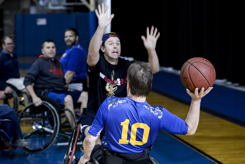 Phil Hogue, from Nephi, Utah, brother of Master. Sgt. Samuel Hogue, 445th Security Forces Squadron, attempts to block a pass by Mr. Keith Cable, Air Force Research Laboratory system administrator, during the 2nd annual wheelchair basketball game held as part of the National Disability Awareness Month activities, Oct. 26, at Wright-Patterson Air Force Base. Hogue who was visiting his brother took the opportunity to participate in this awareness month activity to feel what it is like to play this popular sport while bound to a wheelchair. (U.S. Air Force photo/ Wesley Farnsworth)