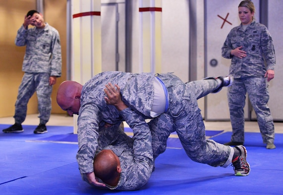 Airman 1st Class Tristan Ecalena escapes the grasp of Staff Sgt. Nicholas Burdick during 50th Security Forces Squadron combatives training at Schriever Air Force Base, Colorado, Monday, Oct. 31, 2016. The training comprises restraint, escape, submission and weapons retention. (U.S. Air Force photo/Brian Hagberg)