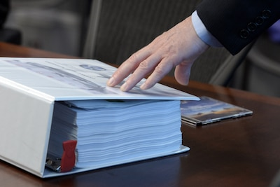 A hand rests on a display symbolizing how massive binders of financial tracking information paper trails have been pared down to software that can fit onto a single compact disc during a briefing at the Pentagon about F-35 cost tracking software developed by the Defense Department and contractor Lockheed Martin, Nov. 1, 2016. DoD photo by EJ Hersom