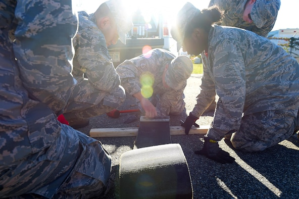 Members of the 633rd Civil Engineer Squadron participate at an electrical power production station during a Prime Base Engineering Emergency Force training at Joint Base Langley-Eustis, Va., Oct. 25, 2016. At this station, which was one of 12, they punched out and reeved nylon purchase tape through a tape connector. (U.S. Air Force photo by Senior Airman Kimberly Nagle)