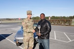 "Army Col. Brad Eungard, DLA Distribution Susquehanna, Pa., commander presents Henry Johnson the ""Rusty Piston"" for his first place Corvette at the CFC Car Show on October 28."
