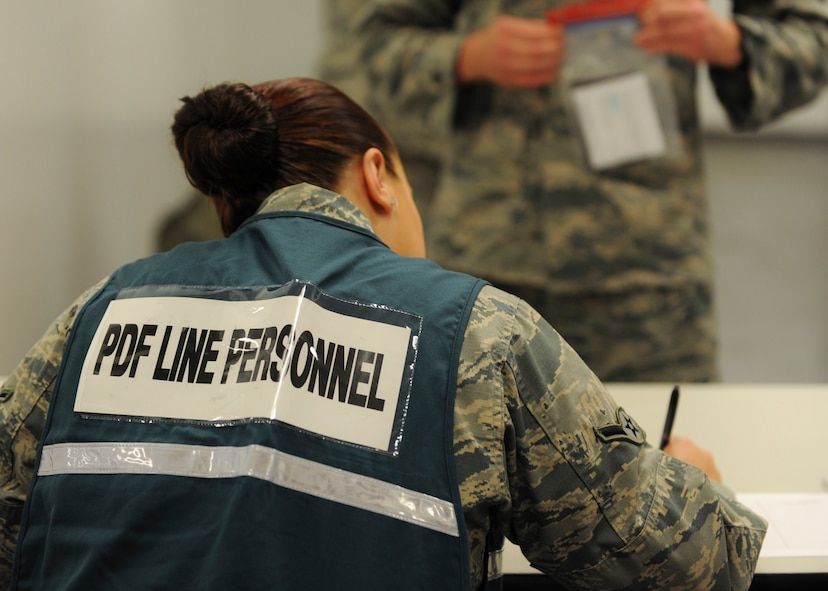 A member of the personnel deployment function (PDF) line checks the identification of a deployer during Exercise Global Thunder 17 (GT17) at Whiteman Air Force Base, Mo., Oct. 26, 2016. Exercises like GT17 involve extensive planning and coordination to provide unique training opportunities for assigned units and forces. (U.S. Air Force by Senior Airman Danielle Quilla)