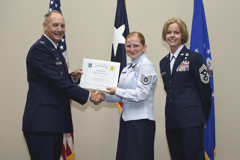 U.S. Air Force Col. Michael Downs, 17th Training Wing Commander, and Chief Master Sgt. Bobbie Riensche, 17th TRW Command Chief, present the NCO of the Quarter award to Tech. Sgt. Jessi Baugh, 17th Medical Support Squadron, during the wing quarterly awards ceremony at the Event Center on Goodfellow Air Force Base, Texas, Oct. 31, 2016. (U.S. Air Force photo by Airman 1st Class Chase Sousa/Released)