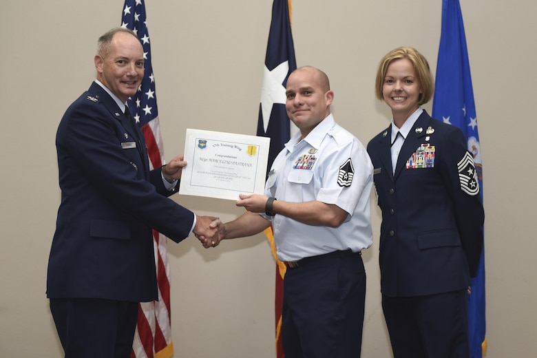 U.S. Air Force Col. Michael Downs, 17th Training Wing Commander, and Chief Master Sgt. Bobbie Riensche, 17th TRW Command Chief, present the Senior NCO of the Quarter award to Master Sgt. Marcelino Pastrana, 17th Contracting Squadron, during the wing quarterly awards ceremony at the Event Center on Goodfellow Air Force Base, Texas, Oct. 31, 2016. (U.S. Air Force photo by Airman 1st Class Chase Sousa/Released)