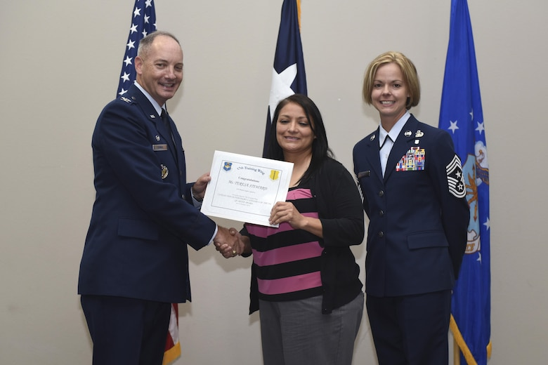 U.S. Air Force Col. Michael Downs, 17th Training Wing Commander, and Chief Master Sgt. Bobbie Riensche, 17th TRW Command Chief, present the Civilian Category I Non-Supervisory of the Quarter to Teresa Steward, 17th Medical Support Squadron, during the wing quarterly awards ceremony at the Event Center on Goodfellow Air Force Base, Texas, Oct. 31, 2016. (U.S. Air Force photo by Airman 1st Class Chase Sousa/Released)