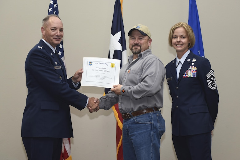 U.S. Air Force Col. Michael Downs, 17th Training Wing Commander, and Chief Master Sgt. Bobbie Riensche, 17th TRW Command Chief, present the Civilian Category II Non-Supervisory of the Quarter Christopher Hill, 17th Training Support Squadron, during the wing quarterly awards ceremony at the Event Center on Goodfellow Air Force Base, Texas, Oct. 31, 2016. (U.S. Air Force photo by Airman 1st Class Chase Sousa/Released)
