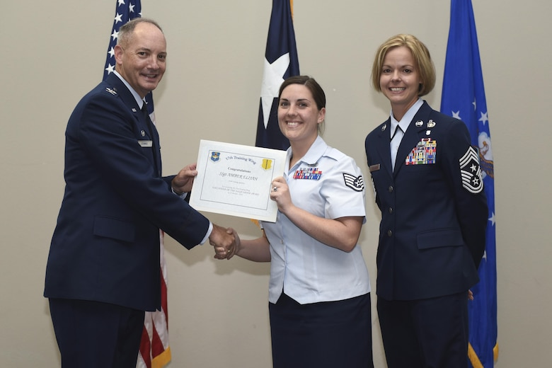 U.S. Air Force Col. Michael Downs, 17th Training Wing Commander, and Chief Master Sgt. Bobbie Riensche, 17th TRW Command Chief, present the Volunteer of the Quarter to Staff Sgt. Amber Elijah, 315th Training Squadron, during the wing quarterly awards ceremony at the Event Center on Goodfellow Air Force Base, Texas, Oct. 31, 2016. (U.S. Air Force photo by Airman 1st Class Chase Sousa/Released)