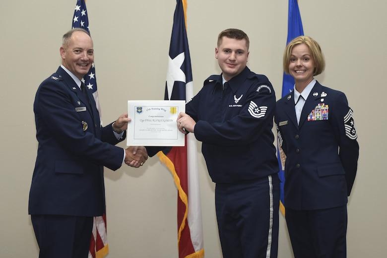 U.S. Air Force Col. Michael Downs, 17th Training Wing Commander, and Chief Master Sgt. Bobbie Riensche, 17th TRW Command Chief, present the Honor Guard Member of the Quarter to Tech. Sgt. Paul Klingensmith, 316th Training Squadron, during the wing quarterly awards ceremony at the Event Center on Goodfellow Air Force Base, Texas, Oct. 31, 2016. (U.S. Air Force photo by Airman 1st Class Chase Sousa/Released)