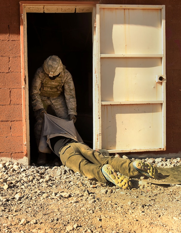 An Airman assigned to the 799th Security Forces Squadron drags a neutralized member of the opposing force into a building during a Fundamentals of Proficiency Fire and Close Quarters Battle course, Oct. 21, 2016, at Range 63C, Silver Flag Alpha, Nev. Members of the Nellis and Creech Air Force Base community volunteered to assist in simulating scenarios in a deployed environment. (U.S. Air Force photo by Airman 1st Class James Thompson)