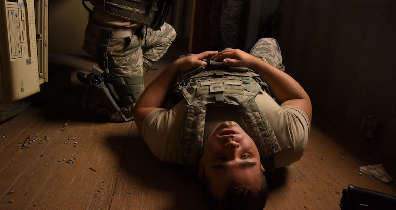 An Airman assigned to the 799th Security Forces Squadron simulates a gunshot wound during a training exercise, Oct. 3, 2016, at Range 63C, Silver Flag Alpha, Nev.  Along with close quarters battle techniques, Airmen were trained on combat life support through a multitude of scenarios. (U.S. Air Force photo by Airman 1st Class James Thompson)