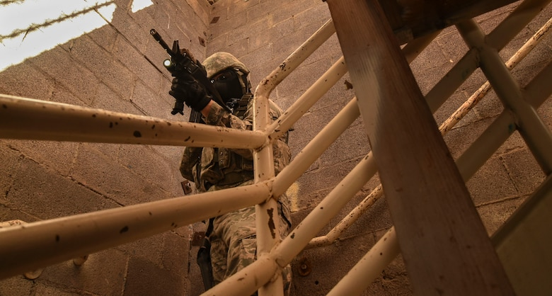 An Airman assigned to the 799th Security Forces Squadron guards the stairs as a fire team attempts to clear a building during the field training exercise of a Fundamentals of Proficiency Fire and Close Quarters Battle course, Oct. 21, 2016, at Range 63C, Silver Flag Alpha, Nev. Volunteers from Nellis and Creech Air Force Bases acted as locals and opposing forces in a mock-deployment environment for the exercise. (U.S. Air Force photo by Airman 1st Class James Thompson)