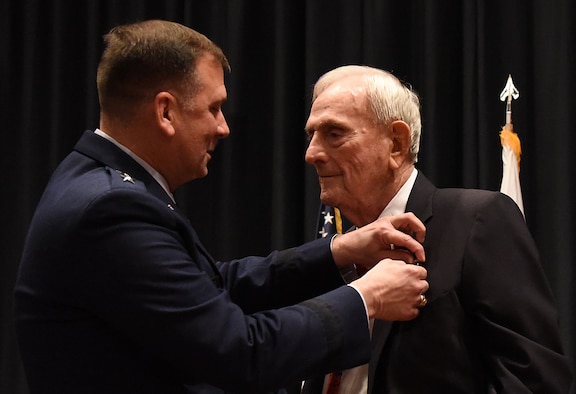 "Maj. Gen. Christopher Bence, U.S. Air Force Expeditionary Center commander, pins the Silver Star on Maj. William ""Joe"" Schneider during a ceremony on Joint Base McGuire-Dix-Lakehurst, Nov. 1, 2016, for his actions while commanding an 18-plane bombing raid on Feb. 23, 1945 over Italy. (U.S. Air Force photo by Tech. Sgt. Jamie Powell)"