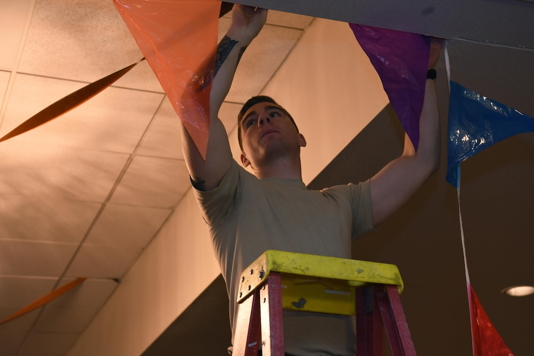 Senior Airman Daniel Tinsley, 790th Missile Security Forces Squadron tactical response force assaulter, hangs up decorations in the Trail's End at F.E. Warren Air Force Base, Wyo., Oct. 27, 2016. Tinsley and other Airmen helped set up for an upcoming event. (Airman 1st Class Breanna Carter)