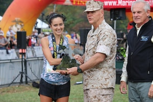 Army Capt Meghan Curran receives the 2nd Place Marine Corps Marathon award from the Commandant of the Marine Corps, General Robert Neller. The 2016 Armed Forces Marathon is held in conjunction with the 41st Marine Corps Marathon on 30 October in Washington, D.C.
