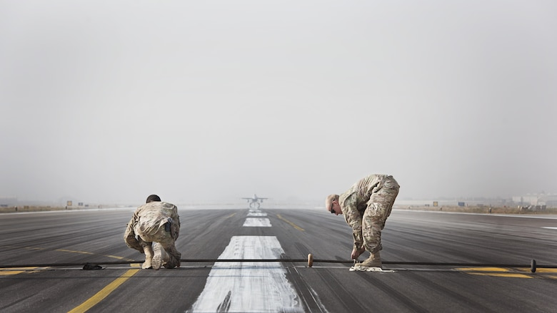 Senior Airmen Mathew Chapman and Devin Tillman, 455th Expeditionary Civil Engineer Squadron power production specialists, place a Mobile Aircraft Arresting System cable across the runway at Bagram Airfield Afghanistan, during a certification test Oct. 30, 2016. The MAAS is a barrier used to catch the arresting hook on fighter aircraft in case of malfunction upon landing or take off. (U.S. Air Force photo by Staff Sgt. Katherine Spessa)