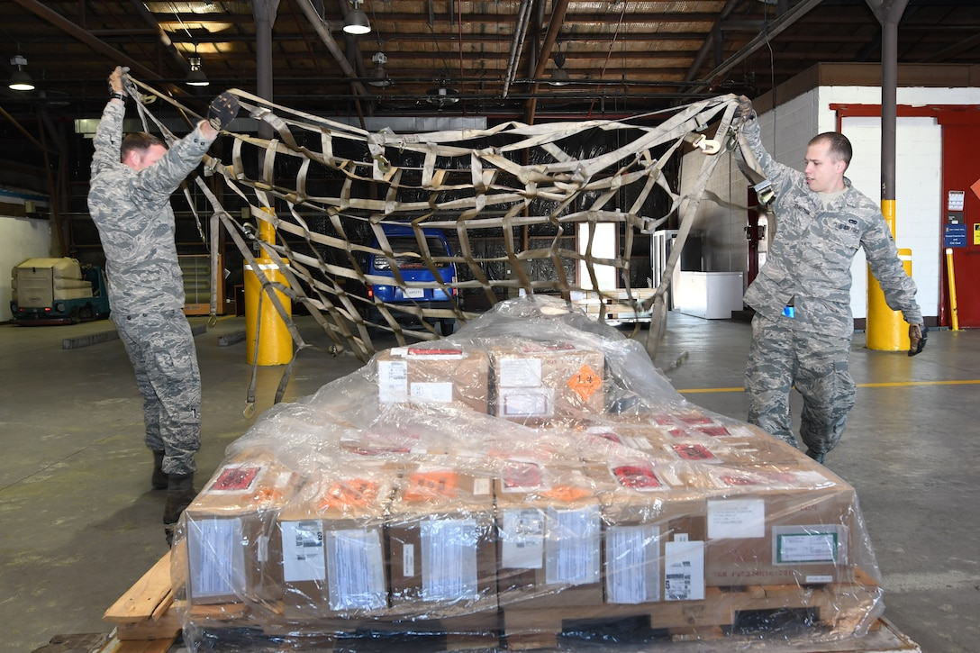 U.S. Air Force Staff Sgt. Richard Allen, 731st Air Mobility Squadron special planning supervisor, and Airman 1st Class Kevin Johnston, 731st AMS special planning technician, toss a securing net over an ammunitions shipping build during routine shipping operations at Osan Air Base, Republic of Korea, Nov. 2, 2016. The special handlers provide storage and shipping requirements for critical military items across the Korean Peninsula. (U.S. Air Force photo by Senior Airman Dillian Bamman)