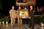 Dan Schultz (right), president of Sikorsky Aircraft, presented a commemorative plaque for the delivery of the 1000th Blackhawk delivery to the Army to Defense Contract Management Agency Sikorsky's commander, Marine Col. Jack Perrin (far left), and Army Col. William Jackson, Utility Helicopter Program Office program manager, during an Oct. 13 ceremony in Stratford, Connecticut. (Photo courtesy of Stuart Walls and Sikorsky Aircraft)