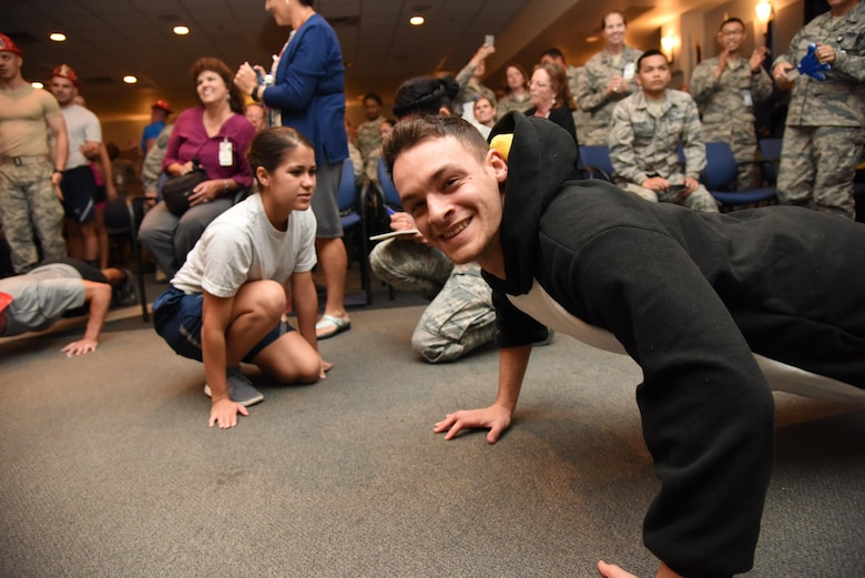 Airman 1st Class Garrett Redmond, 81st Diagnostic and Therapeutics Squadron radiology technician, smiles while doing push-ups during the 81st Medical Group Push-up Competition at the Keesler Medical Center Don Wylie Auditorium Nov. 1, 2016, on Keesler Air Force Base, Miss. Seven five-person teams competed in the event pushing out a total of 6,272 push-ups. The 81st Dental Squadron was this year's winner with 1,127 push-ups. The Airmen who participated in the event raised money to support the Krewe of Medics Mardi Gras Ball. (U.S. Air Force photo by Kemberly Groue/Released)