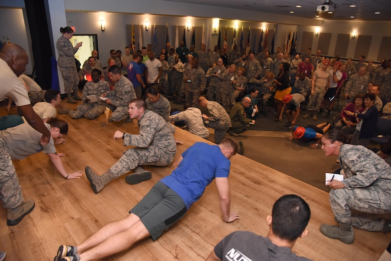 Members of the 81st Medical Group participate in the 81st MDG Push-up Competition at the Keesler Medical Center Don Wylie Auditorium Nov. 1, 2016, on Keesler Air Force Base, Miss. Seven five-person teams competed in the event pushing out a total of 6,272 push-ups. The 81st Dental Squadron was this year's winner with 1,127 push-ups. The Airmen who participated in the event raised money to support the Krewe of Medics Mardi Gras Ball. (U.S. Air Force photo by Kemberly Groue/Released)