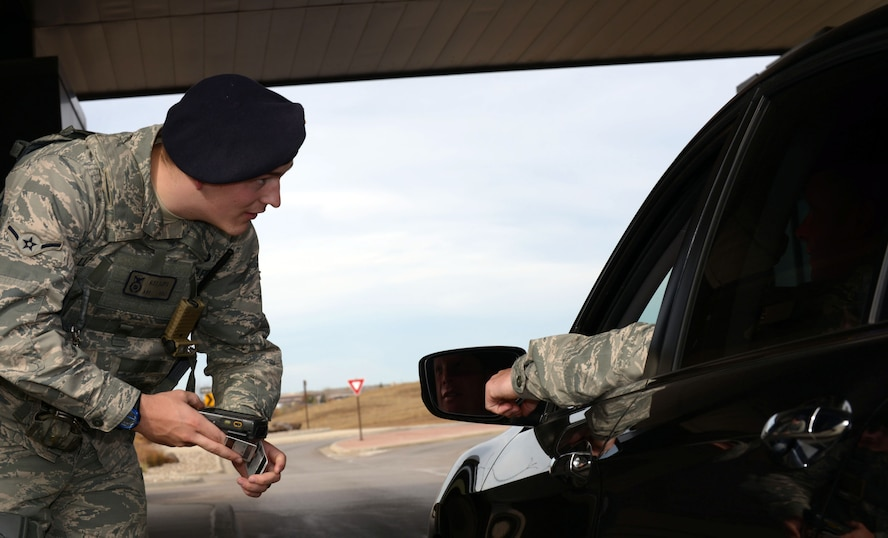 Airman Alex Lloyd, a response force member assigned to the 28th Security Forces Squadron, clears an Airman for entry at the Liberty Gate at Ellsworth AFB, S.D., Oct. 27, 2016. Defenders guard the gate 24 hours a day to ensure the base is secure. (U.S. Air Force photo by Airman 1st Class Donald Knechtel)