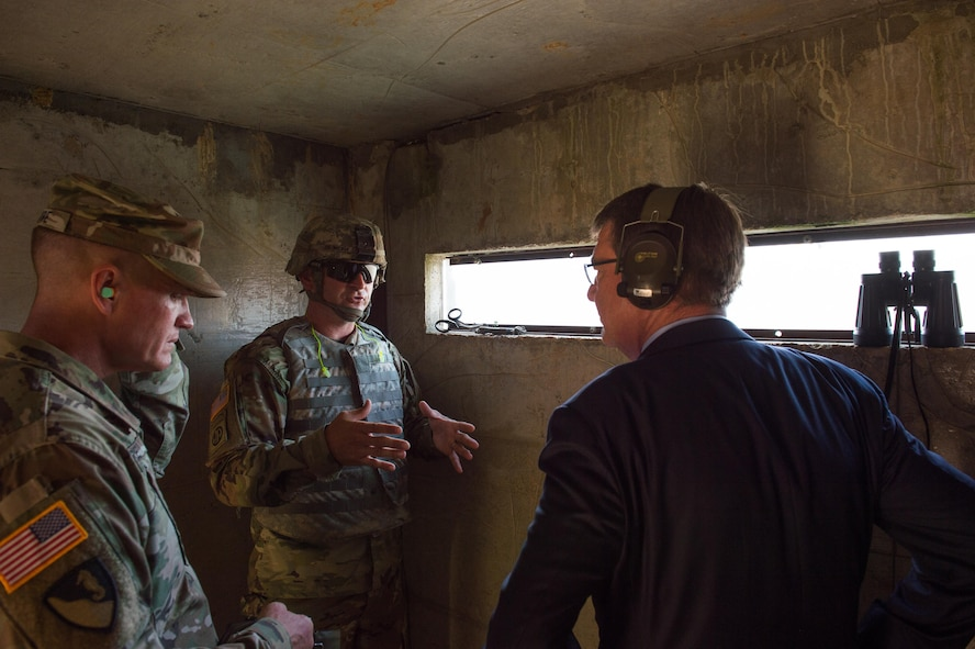 Defense Secretary Ash Carter receives a briefing during a demolition exercise at Fort Leonard Wood.