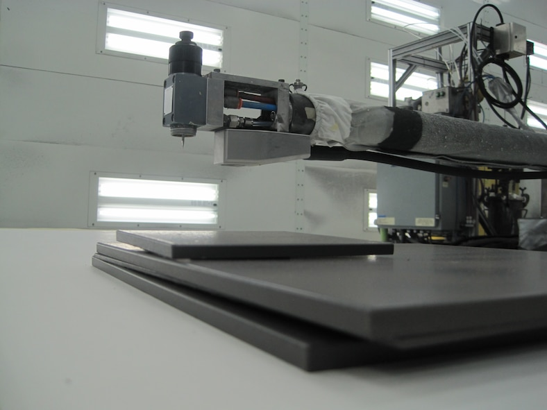 AFRL completed a series of tests to enable the use of the Terahertz Coating Thickness tool, shown here mounted on a robotic arm along with a spray attachment, for F-35 inlet production.  This tool is a non-contact, non-destructive device that allows users to measure coating thickness quickly and easily without risk of damage to coating surfaces.  (Photo courtesy of Northrop Grumman Corp. and Picometrix, LLC)